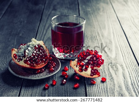 Ripe pomegranate with glass of pomegranate juice on dark wooden table. Toned. - stock photo