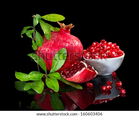 Ripe pomegranate with the branch isolated with mirror image on black background. - stock photo
