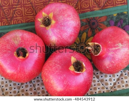 Ripe pomegranates close-up on decorative patterned tablecloth