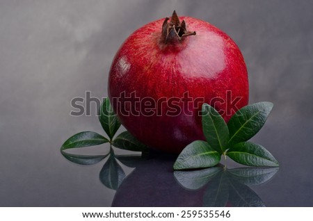 Ripe pomegranates with leaves  on a dark background. photo with reflection - stock photo