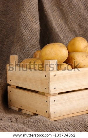 Ripe potatoes in wooden box on sacking - stock photo