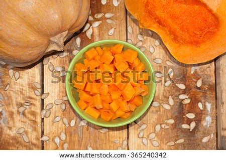 Ripe pumpkin cut on slices on a wooden background. Pieces of pumpkin in a bowl. - stock photo