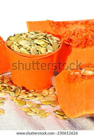 ripe pumpkin with pumpkin seeds in the orange bucket isolated on white background - stock photo
