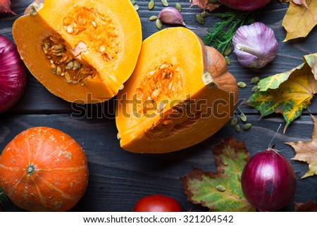 Ripe pumpkins and autumn leaves on wooden background - stock photo