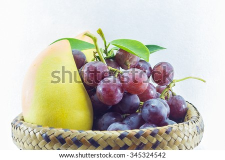 Ripe purple grapes on white background, Ripe mango on white background, Ripe mango and purple grapes in the basket, Fruit healthy.