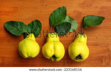 ripe quinces on wooden table  - stock photo