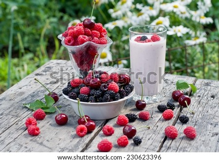 ripe raspberries and cherries on a wooden table in the garden - stock photo
