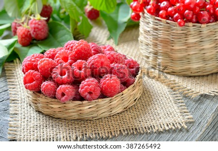 Ripe raspberries in wicker basket on wooden table - stock photo
