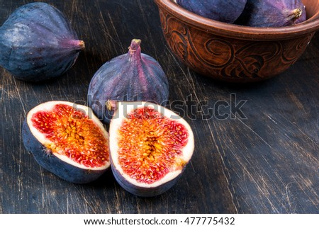 Ripe raw figs on a black wooden table, copy space