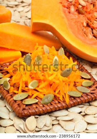 ripe raw pumpkin with grated pumpkin and pumpkin seeds background - stock photo