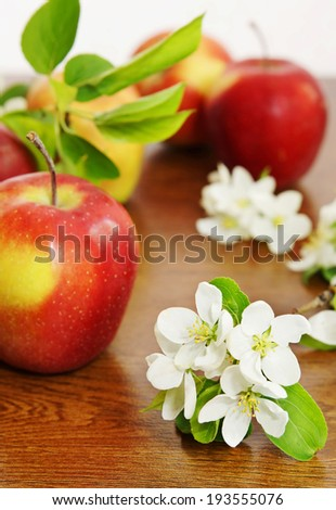 Ripe red apple fruits and apple flower on the wooden board - stock photo