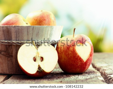 Ripe red apple still life display with a halved apple and an apple with a heart cutout leaning against a wooden tub filled with whole fruit. Visit my portfolio for whole series. - stock photo