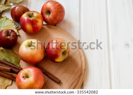Ripe red apples autumn harvest on a wooden background  and  leaves of the trees - stock photo