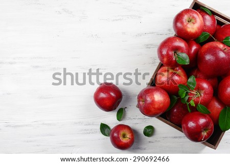 Ripe red apples in crate on wooden background - stock photo