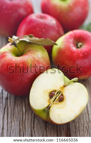 Ripe red apples on an old wooden board. - stock photo