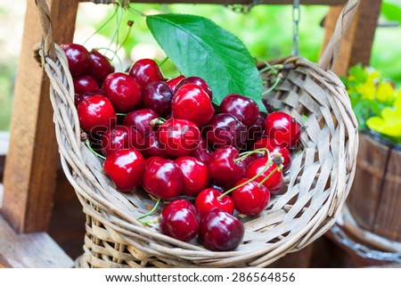 Ripe red cherries in small basket - stock photo