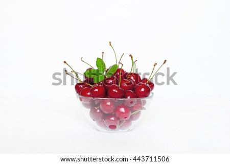 Ripe red juicy cherries with mint leaves in glass bowl on white background closeup. The natural background. - stock photo