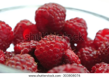 Ripe red juicy raspberries in a glass bowl on white background. Concept of organic food; fresh, natural, healthy, unprocessed fruit: clean eating; paleo diet. - stock photo