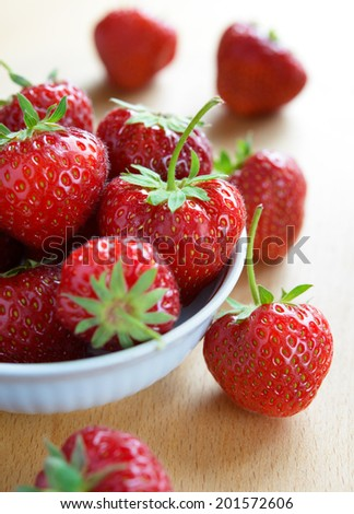 Ripe Red Juicy Strawberries in the White Bowl on the Wooden Table - stock photo