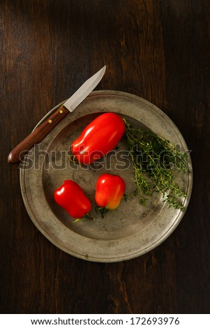 Ripe, red plum tomatoes on a rustic pewter plate accented with Thyme.  Copy space above and below. - stock photo