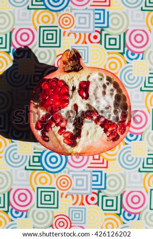 ripe red pomegranate on colored trendy background, summer healthy concept - stock photo