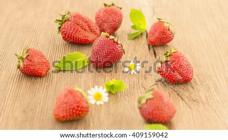Ripe red strawberries and small daisy flowers on a wooden background. Strawberries over wooden table background. - stock photo