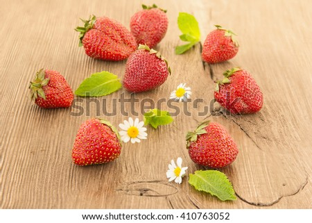 Ripe red strawberries and small daisy flowers on a wooden background. Strawberries over wooden table background with copy space. - stock photo