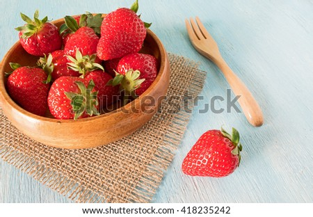 Ripe red strawberries in bowl on wooden table, close up - stock photo