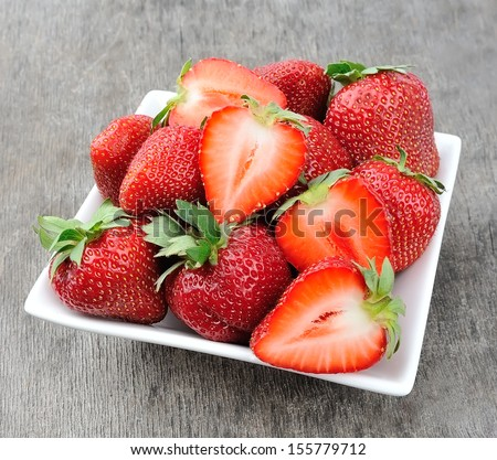 ripe red strawberries on an old wooden textured table  - stock photo