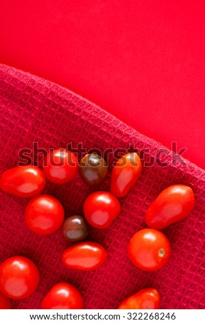 Ripe shiny red and brown cherry tomatoes lying on a red kitchen towel on a red red table. Top view. Different shades of red. - stock photo