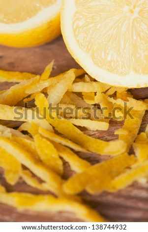 Ripe sliced lemon with lemon peels (zest). Shallow depth of field. - stock photo