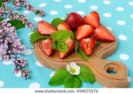 Ripe sliced strawberries. Green strawberry leaves. Rounded kitchen Board light wood. Cooking food. Tablecloth pale turquoise. Branch of lilac blossoms.