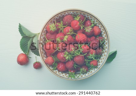 Ripe strawberries in a clay plate on a white wooden board. Top view. Color toning. Low contrast. - stock photo