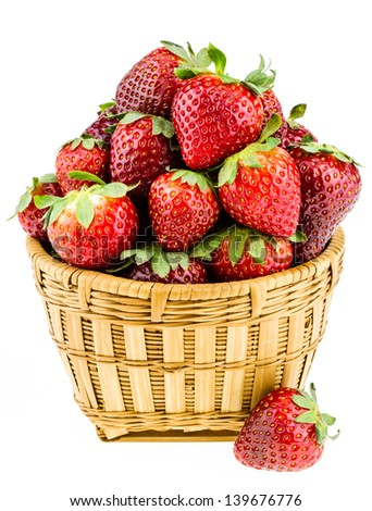 Ripe strawberries piled high in a wicker basket isolated against a white background.