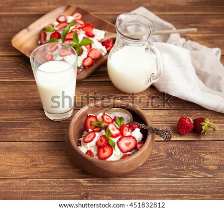 Ripe strawberry, cottage cheese and milk. Farmer products. Food composition on a wooden background. Selective focus - stock photo