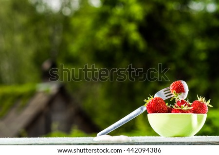 Ripe strawberry in a bowl on wooden table on blurred foliage background. - stock photo