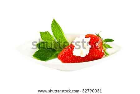 Ripe strawberry with cream on a white plate