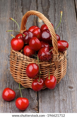 Ripe Sweet Cherries in Wicker Basket isolated on Rustic Wooden background - stock photo