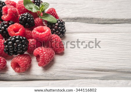 Ripe sweet raspberries and blackberries on wood table background - stock photo