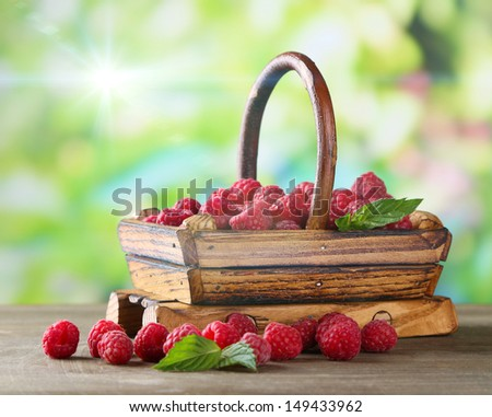 Ripe sweet raspberries in basket on wooden table, on green background - stock photo