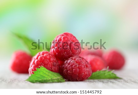 Ripe sweet raspberries on wooden table, on green background - stock photo