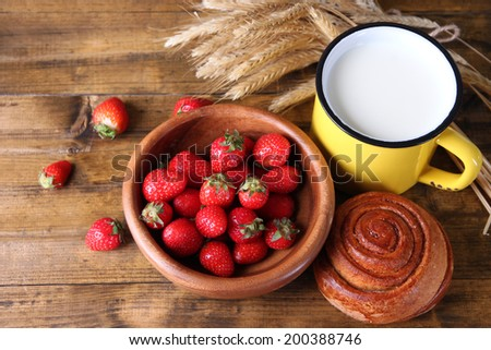 Ripe sweet strawberries, fresh bun and mug with milk on color wooden background