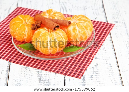 Ripe sweet tangerines with spices on color plate, on napkin, on wooden background