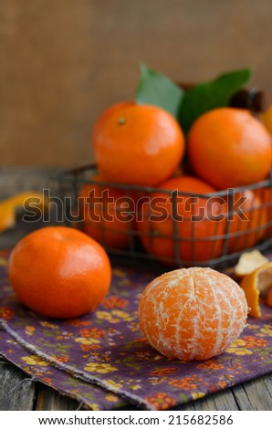 Ripe tangerine fruit and wire basket full of mandarines on wooden background - stock photo