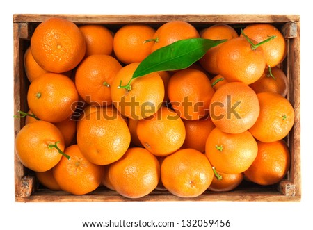 Ripe tangerines with leaves in box on white background - stock photo