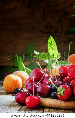 Ripe tasty summer fruits and berries with leaves on the old wooden table, still life in rustic style, selective focus - stock photo