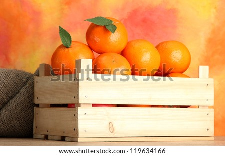 Ripe tasty tangerines with leaves in wooden box on table on orange background - stock photo