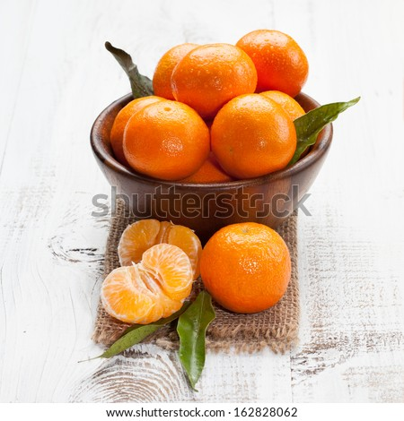 Ripe tasty tangerines with leaves on a white wooden table - stock photo