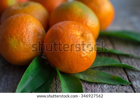 Ripe tasty tangerines with leaves on old wooden table. mandarine  - stock photo