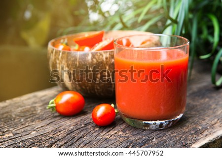 Ripe tomatoes and glass of tomato juice on wooden table